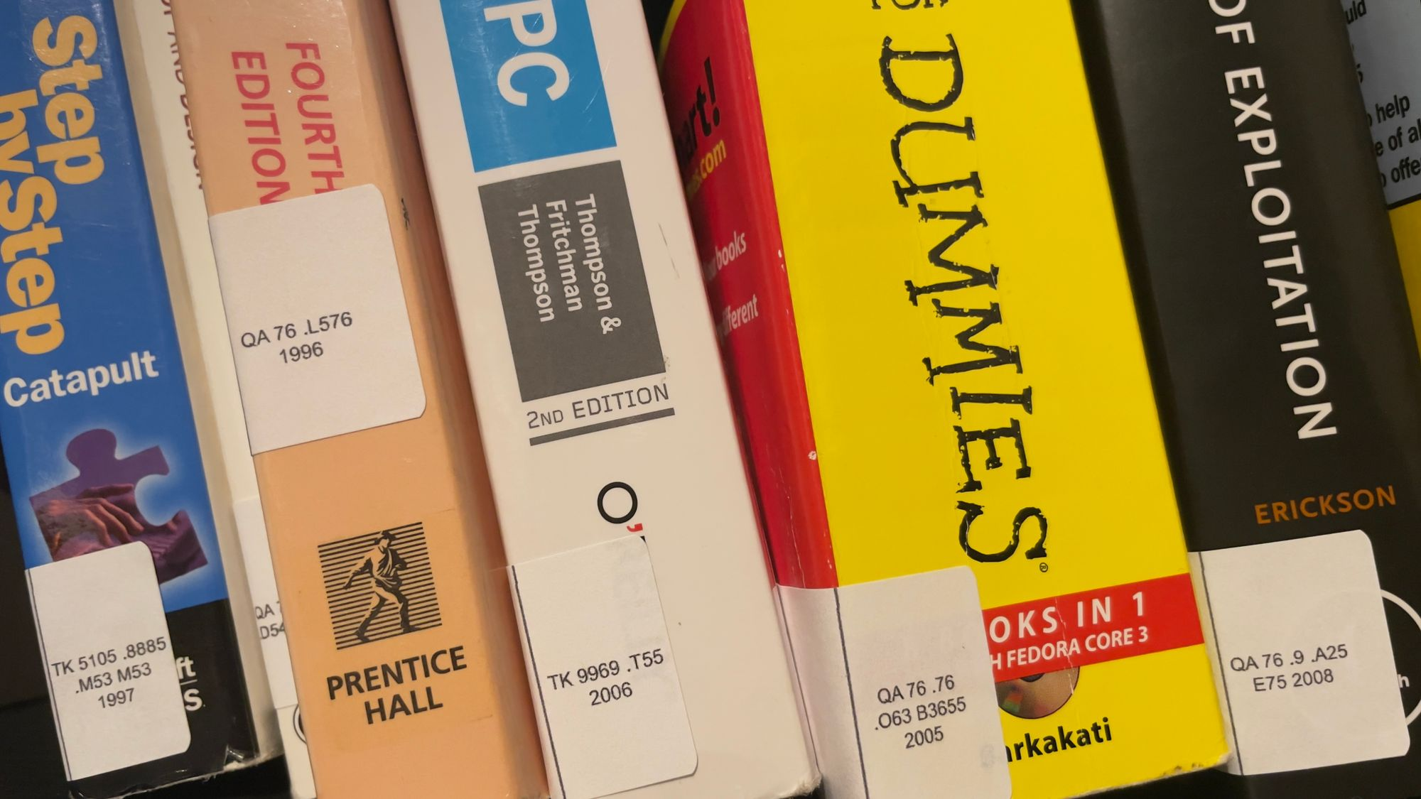 5 books sitting on a bookshelf, each with stickers on their spines showing a Library of Congress Classification number